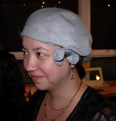 Christine is wearing a fabric beret with flower trim