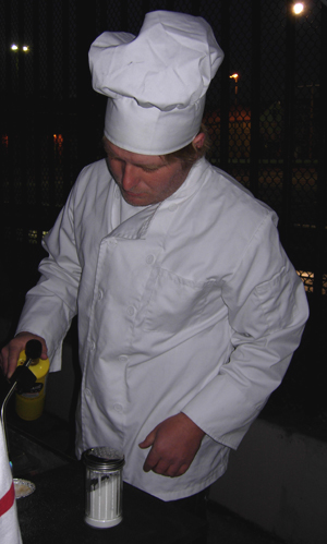 Curtis, in his chef's hat, torching creme brulee